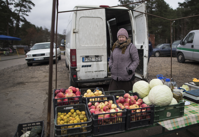 A vendor waits for customers at a market in Visaginas, a Lithuanian town heavily populated by ethnic Russians, some 150 km (93 miles) northeast of the capital Vilnius, Lithuania, Sunday, Nov. 27, 2016. Across the Baltic states of Lithuania, Latvia and Estonia, people fear Russia's large military buildup of forces and nuclear-capable missiles in Russia's Kaliningrad region and have raised questions about the loyalties of the ethnic Russians in the country, who make up about 6 percent of the population. (AP Photo/Mindaugas Kulbis)