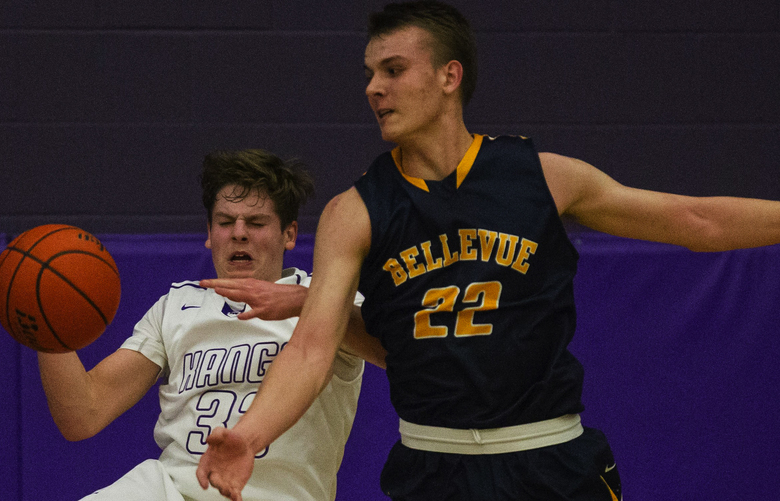 It's a furious battle for the rebound underneath the Bellevue bucket with neither Lake Washington's ASam Linseky (left) or Bellevue's Andrew Kenny being able to take possession in the 2nd quarter.  Bellevue basketball played at Lake Washington Thursday, December 17, 2015.