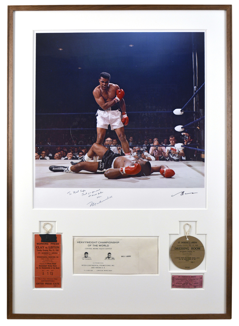 This undated photo provided by Guernsey's shows a 1965 photo by Neil Leifer of Muhammad Ali towering over a fallen Sonny Liston during their World Heavyweight title bout, framed with Leifer's press credentials for the fight and signed by Ali. Hundreds of Leifer's photos, as well photos he collected by other photographers, are going on the auction block in New York City. (Guernsey's via AP)