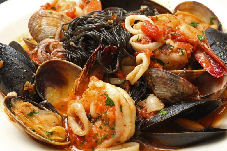 Carmine's squid ink capellini di mare (angel hair pasta tossed with tomatoes, prawns, mussels, calamari and Manila clams). (Ken Lambert/The Seattle Times)