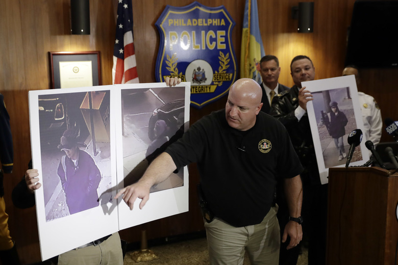 Philadelphia Police Det. Timothy Brooks discusses an image made from video of person of interest with members of the media during a during a news conference at Police Headquarters in Philadelphia, Thursday, Dec. 1, 2016. Authorities have confirmed that a package that blew up when a Philadelphia man opened it contained a homemade explosive. They also announced Thursday that they have video of the person who dropped off the package at the home of 60-year-old James Alden, who was seriously wounded in the Nov. 22 blast. (AP Photo/Matt Rourke)