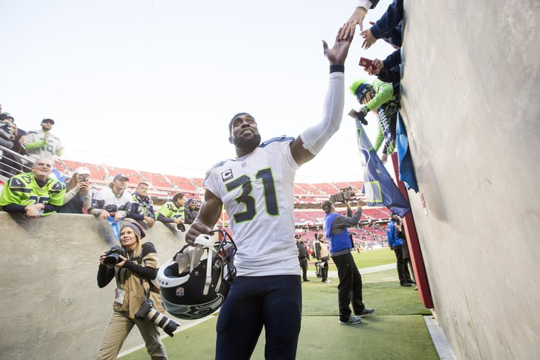 Seahawks safety Kam Chancellor high fives fans after the Seahawks beat the San Francisco 49ers 25-23 at Levi Stadium in Santa Clara, California, earlier this month. (Bettina Hansen / The Seattle Times)