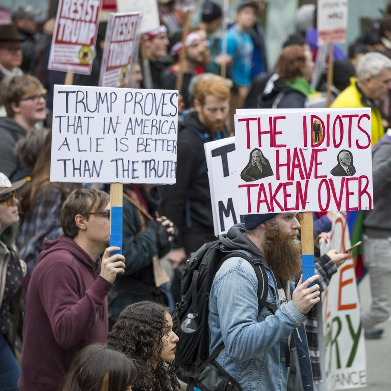 Anti-Trump signs abound at the All United, None Divided Immigrant Rights March sponsored by El Comité.   (Bettina Hansen / The Seattle Times)
