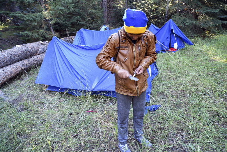 In this Sept. 10, 2016, photo, Tapas Khanal, a 13-year-old refugee from south Asia, whittles a stick at his campsite in Evergreen, Colo. He belongs to a Boy Scout troop in Aurora, Colo., that is made up almost entirely of refugees who hail from far-flung places like Burma, Rwanda and Nepal. (AP Photo/Thomas Peipert)