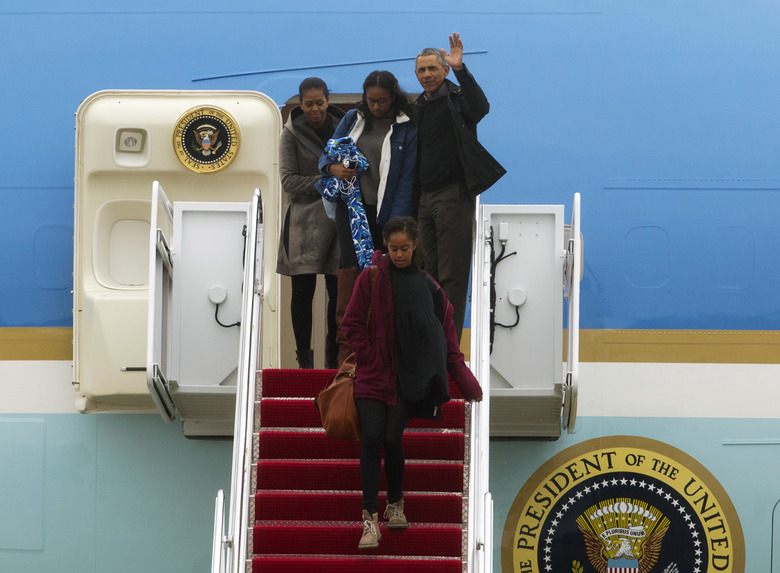 President Barack Obama accompanied by first lady Michelle Obama and his daughters Malia and Sasha, waves from Air Force One, upon their arrival at Andrews Air Force Base, Md., Monday, Jan. 2, 2017. The President and his family are returning from Hawaii after vacation. ( AP Photo/Jose Luis Magana)