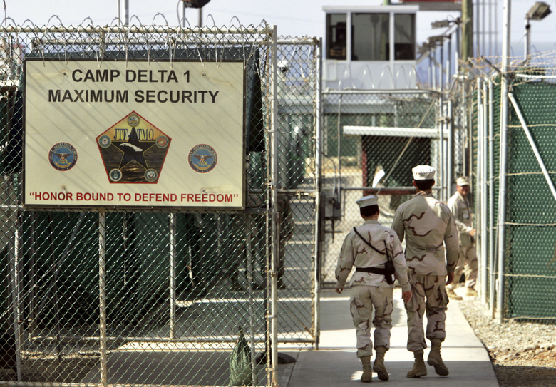 "FILE – In this June 27, 2006 file photo, reviewed by a US Department of Defense official, US military guards walk within Camp Delta military-run prison, at the Guantanamo Bay US Naval Base, Cuba. A draft executive order shows President Donald Trump asking for a review of America's methods for interrogation terror suspects and whether the U.S. should reopen CIA-run ""black site"" prisons outside the U.S.  (AP Photo/Brennan Linsley, file)"