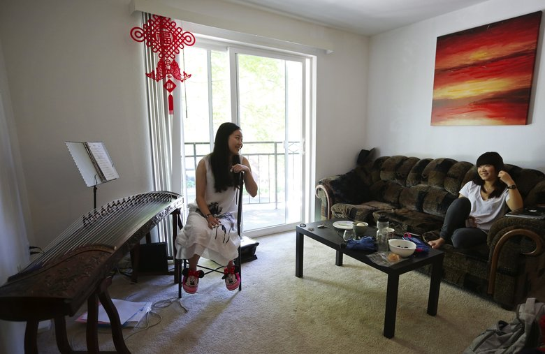 University of Washington roommates from China Rony Huang (graduated), left, who plays a traditional Chinese musical instrument called a guzheng, and Lucy Deng (a junior), right, in their University District apartment. (Ken Lambert/The Seattle Times)