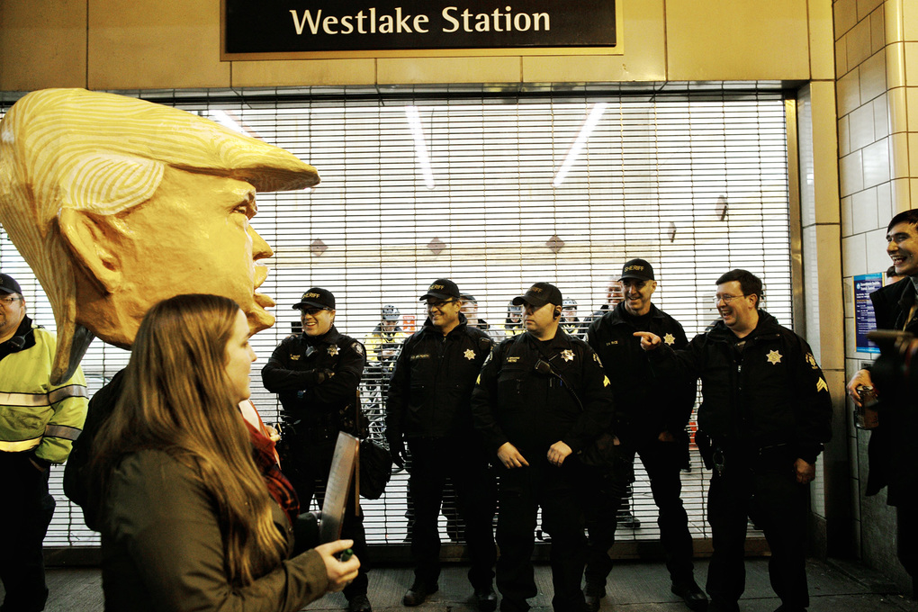 A person wearing a President Donald Trump outfit walks past a row of Seattle police officers during a demonstration on Friday near Westlake Station in Seattle. (Johnny Andrews / The Seattle Times)