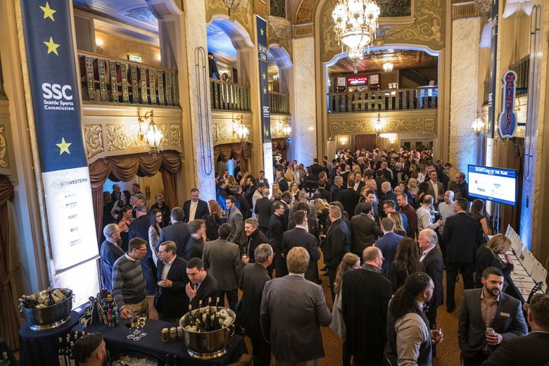 Attendees of the 82nd annual sports awards hang out in the lobby of the Paramount Theater. (Dean Rutz / The Seattle Times)