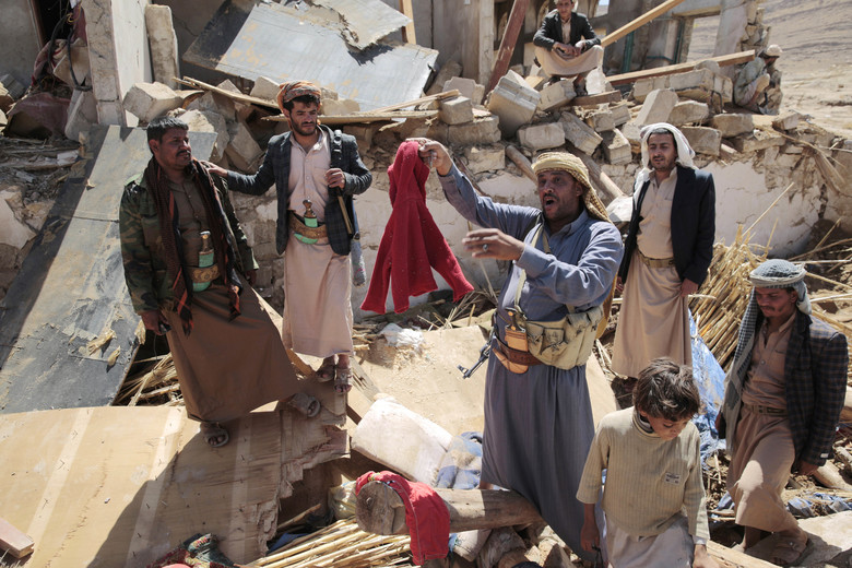 A man center, holds house destroyed by a Saudi-led airstrikes in outskirts of Sanaa, Yemen, Thursday, Feb. 16, 2017. At least one Saudi-led airstrike near Yemen's rebel-held capital killed at least five people on Wednesday, the country's Houthi rebels and medical officials said. (AP Photo/Hani Mohammed)