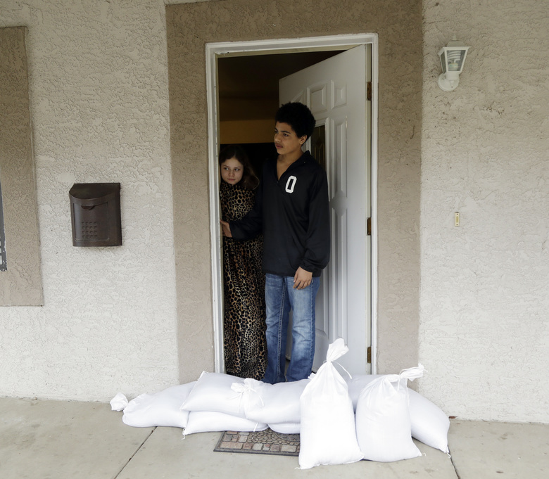 Alexis Ramirez, center left, looks out the door of her home, which has been reinforced with sandbags, alongside her friend Kye Bruhn Wednesday, Feb. 15, 2017, in Oroville, Calif. Many Oroville residents returned home to pack an emergency bag, fill their cars with family valuables and leave. Authorities say the immediate danger has passed and allowed people living downstream of the Oroville Dam to go back home Tuesday after ordering an evacuation Sunday. (AP Photo/Marcio Jose Sanchez)
