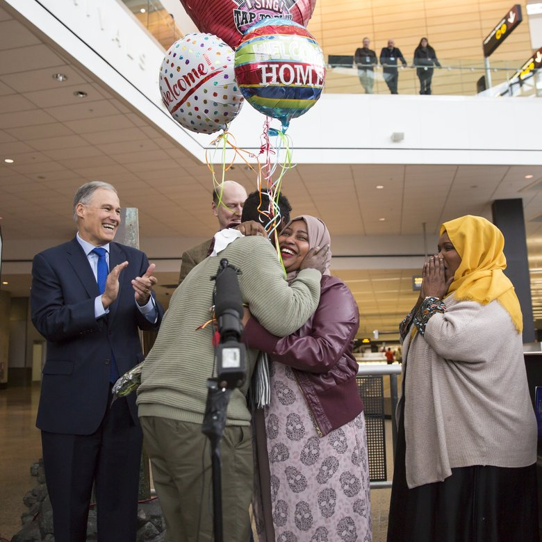 Gov. Jay Inslee applauds as a Somali immigrant, Isahaq Ahmed Rabi, is hugged by family members on his arrival at the Seattle-Tacoma International Airport. Because of the president's executive order on immigration he had earlier been turned away when attempting to join his wife, a U.S. citizen. (Bettina Hansen/The Seattle Times)