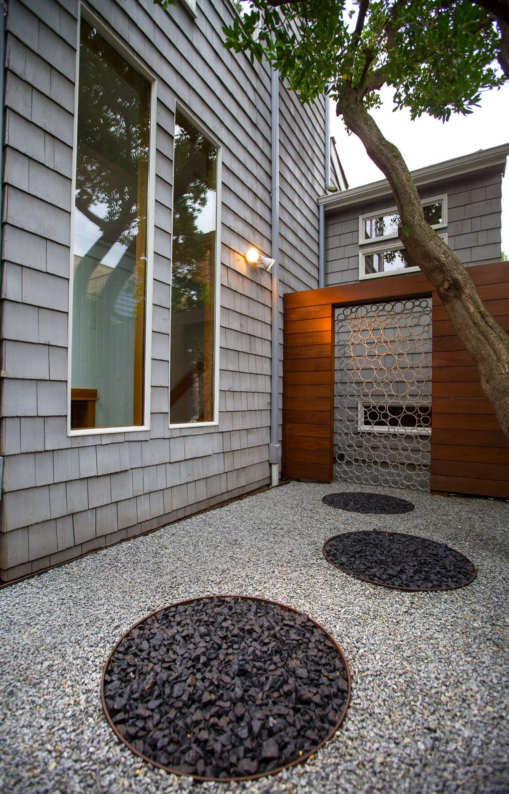 An aluminum gate repeats the circle motif in the side garden, where a simple composition of two tones of gravel, siding, fence and tree adds up to a quiet yet dramatic Zen garden. (Mike Siegel/The Seattle Times)