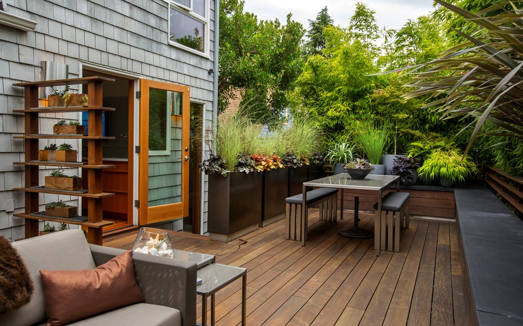 The back door opens wide to a deck that spans the entire back garden, from the house to the bamboo privacy hedge. The al fresco dining room is at the north end of the deck, with the sitting room in the foreground. (Mike Siegel/The Seattle Times)