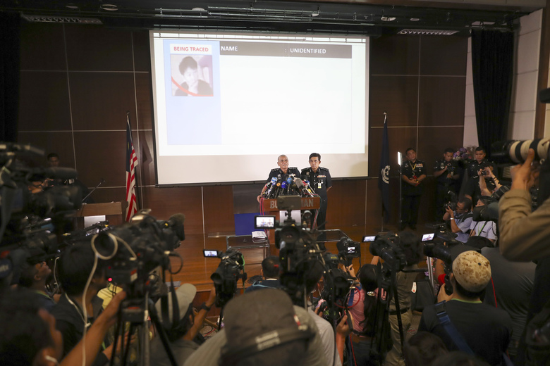 Malaysia Deputy Inspector-General of Police Noor Rashid Ibrahim, center left, shows a picture of one of the suspects during a press conference at police headquarter in Kuala Lumpur, Malaysia, Sunday, Feb. 19, 2017. Investigators are still trying to piece together details of what appears to be the brazen assassination of Kim Jong Nam, the half brother of North Korea's mercurial ruler and an exiled member of the country's elite. (AP Photo/Vincent Thian)