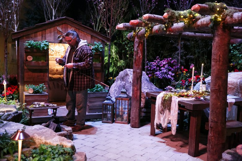 "Jeff Finch, with Choice Landscapes, puts the finishing touches on ""An Evening in The Mountains"" at the show. Ryan Gaither designed the garden with herbs, berry bushes, a warming pit and a waterfall.  (Erika Schultz/The Seattle Times)"