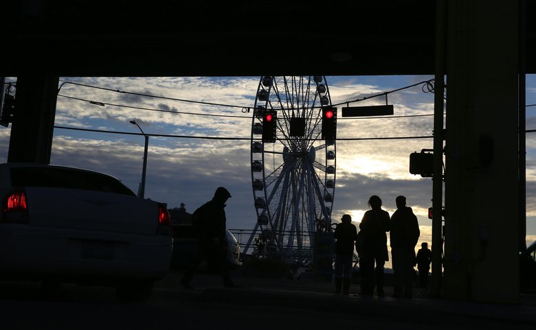 Pedestrians in the shadow of the Viaduct walk past the Seattle Great Wheel on the waterfront. (Ken Lambert/The Seattle Times)