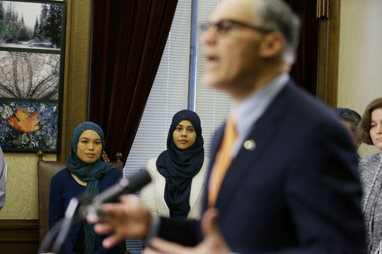 Rokaih Vansot, left, a member of the Washington state chapter of the Council on American-Islamic Relations, with Aishah Bomani, center, principal of Seattle's Makkah Islamic School, as Gov. Jay Inslee, right, explains his signing an executive order to ensure that state workers don't help carry out President Trump's immigration policies.  (Ted S. Warren/The Associated Press)