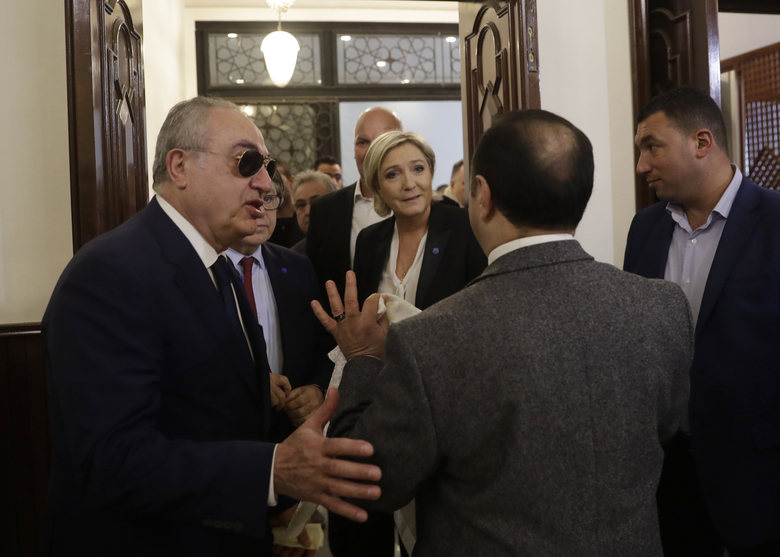 An aide to Lebanon's Grand Mufti Sheikh Abdel-Latif Derian, right, holds a head scarf as he tries to convince French far-right presidential candidate Marine Le Pen, center, to wear it during his meeting with the Mufti but she refused, at Dar al-Fatwa the headquarters of the Sunni Mufti, in Beirut, Lebanon, Tuesday, Feb. 21, 2017. Le Pen refused to go into a meeting with Lebanon's Grand mufti after his aides asked her to wear a head scarf. Le Pen said she met in the past with the Grand mufti of Egypt's Al-Azhar, one of the world's top Sunni clerics, without wearing a veil. Once she was told it is different here, Le Pen walked toward her car and left. (AP Photo/Hussein Malla)
