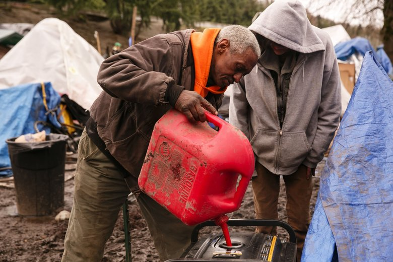 Resident Reavy Washington fills a generator with gasoline before organizing a meeting at the homeless camp where Washington lives at South Royal Brougham Way and Airport Way South in Seattle on Sunday. (Erika Schultz/The Seattle Times)