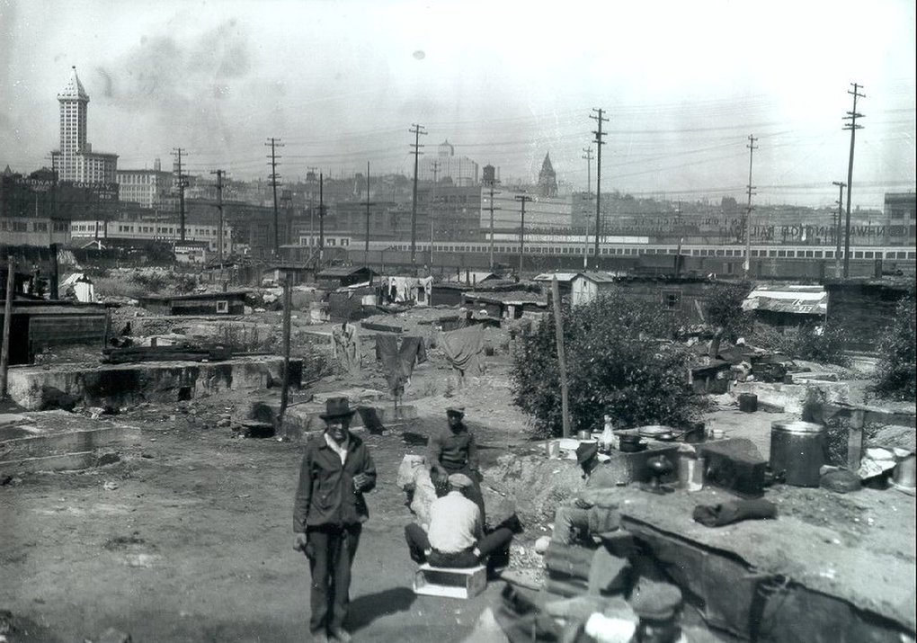 People walk between shacks in Hooverville in 1932. (King County Archives)