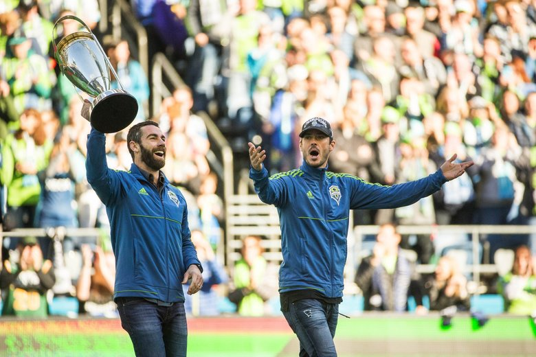 Zach Scott, left, and Brad Evans bring the MLS Cup onto the field for the start of Sunday's game with New York. (Dean Rutz / The Seattle Times)