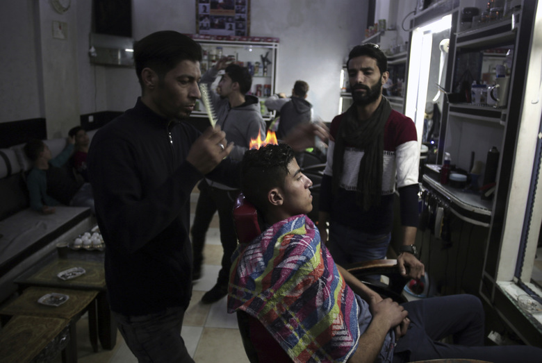 """After cutting and combing, the barber applies what he calls """"special"""" lotion and powder client's heads to protect their skin before using an aerosol can to burn hair off. (AP Photo/ Khalil Hamra)"""
