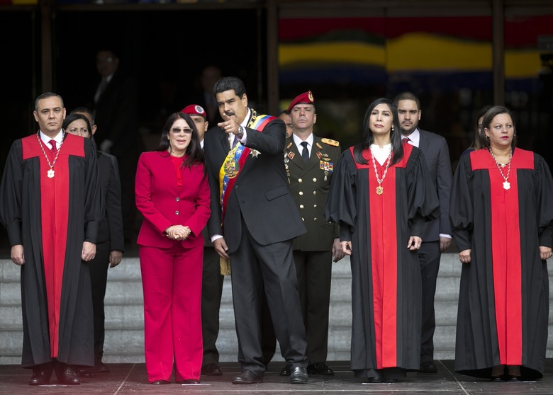 FILE – In this Jan. 15, 2017 file photo, Venezuela's President Nicolas Maduro speaks with first lady Cilia Flores as they arrive to the Supreme Court, before delivering his state of the union address, in Caracas, Venezuela.  Venezuela's Supreme Court ruled Wednesday night, that it can take over responsibilities assigned to Congress. Maduro opponents are saying it's part of an attempt to install a dictatorship in the South American nation. Justices pictured from left to right; Supreme Court Vice President Maikel Moreno; Supreme Court President Gladys Gutierrez; and Supreme Court Justice Indira Alfonso. (AP Photo/Ariana Cubillos, File)