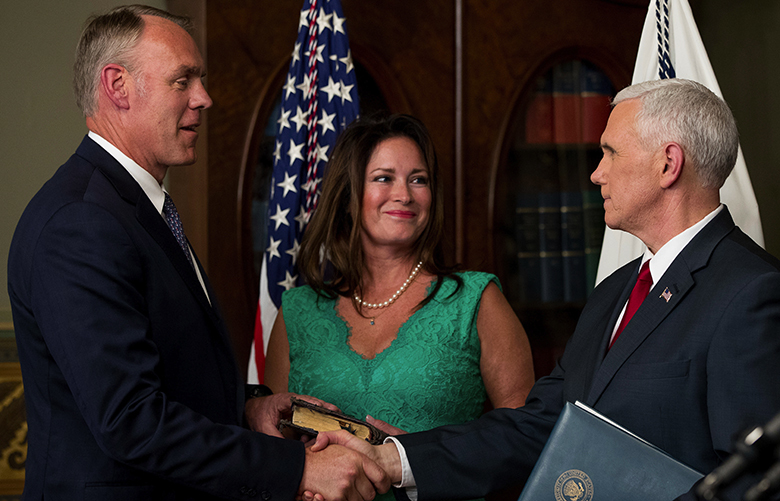 Vice President Mike Pence, right, shakes hands after administering the oath of office to Interior Secretary Ryan Zinke, left, Wednesday, March 1, 2017, in the Eisenhower Executive Office Building on the White House complex in Washington. Also pictured is Ryan Zinke's wife Lolita Hand, center. (AP Photo/Andrew Harnik)