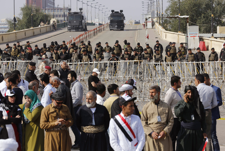"""Iraqi riot police close a bridge leading to the heavily guarded Green Zone during a demonstration of supporters of Iraq's influential Shiite cleric Muqtada al-Sadr against corruption in Tahrir Square in Baghdad, Iraq, Friday, March 24, 2017. Al-Sadr has threatened to boycott the upcoming provincial elections, urging instead followers to join a """"reform revolution."""" (AP Photo/Karim Kadim)"""