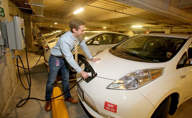 City of Seattle employee Chris Bast, a climate-policy adviser, plugs in a Nissan Leaf electric vehicle. (Greg Gilbert/The Seattle Times)