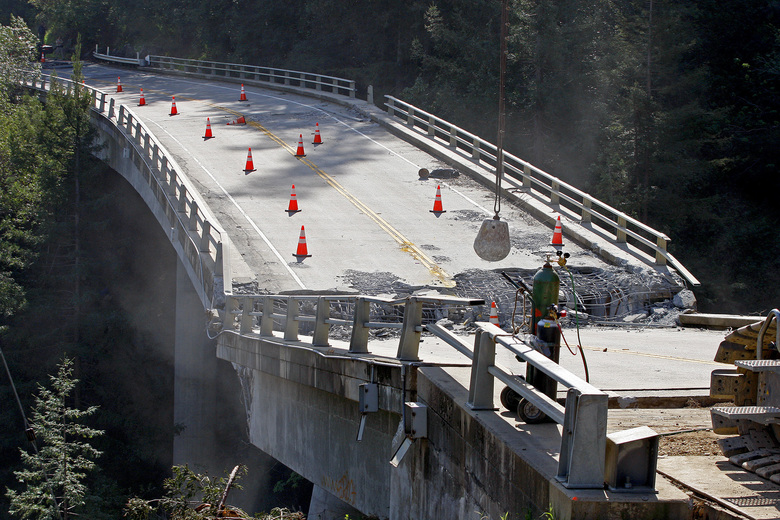 FILE- In this March 16, 2017, file photo, crews use a wrecking ball attached to a crane on the demolition of the storm-damaged Pfeiffer Canyon Bridge in Big Sur, Calif. The crumbling bridge along the California coast has stranded residents in the popular Big Sur area and closed part of iconic Highway 1. (Vern Fisher/Monterey Herald via AP, File)