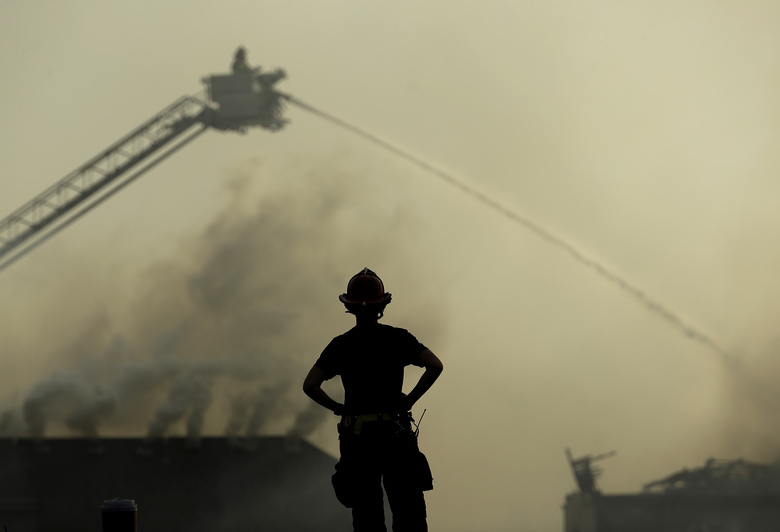 A firefighter watches from the scene of an apartment complex fire as firefighters douse fires at nearby houses Monday, March 20, 2017, in Overland Park, Kan. Once one roof caught fire, embers jumped from roof to roof, spreading the blaze, said Overland Park Fire Department spokesman Jason Rhodes. (AP Photo/Charlie Riedel)