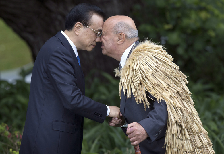 Chinese Premier Li Keqiang, left, receives a hongi, a traditional Maori greeting, from Maori elder Professor Piri Sciascia at Government House in Wellington, New Zealand, Monday, March 27, 2017. Li is on three-day visit to New Zealand for high-level talks at a time that both countries are pushing to expand free trade. (Mark Mitchell/NZ Herald via AP)
