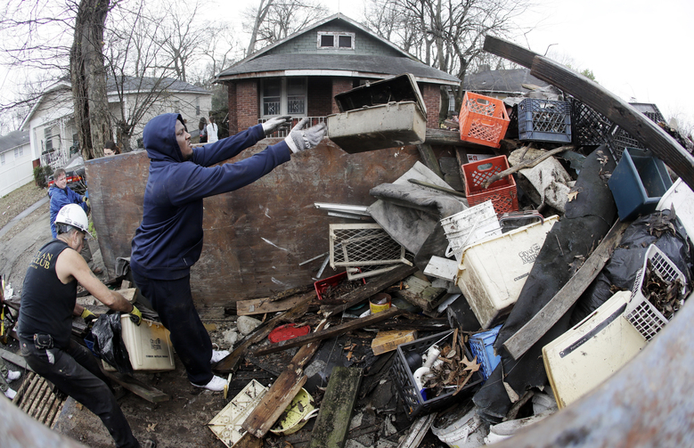 In this Jan. 16, 2017 photo, Martin Lleras, left, and Joshua Cleaves put trash in a dumpster in front of an abandoned home on Martin Luther King Day in Memphis, Tenn. Last year, experts said Memphis became the first U.S. city to draft a charter document that specifically deals with the problem of housing and neighborhood blight. (AP Photo/Mark Humphrey)