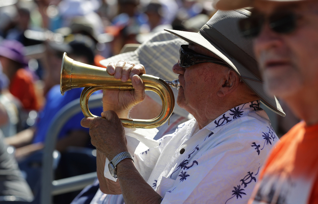 C.W. Cresap plays his horn during the first inning of a spring training baseball game between the Seattle Mariners and the San Francisco Giants, Saturday, March 18, 2017, in Peoria, Ariz. (AP Photo/Darron Cummings)