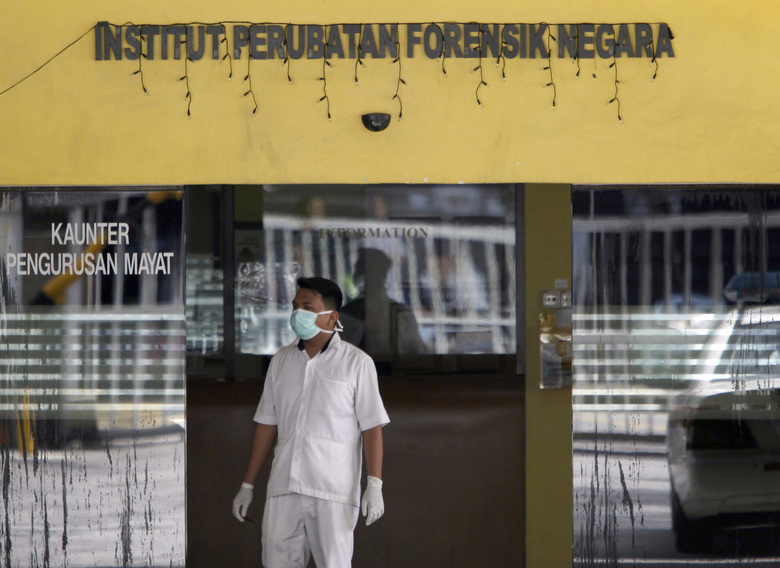 A medical staff member stands outside forensic department at Kuala Lumpur Hospital in Kuala Lumpur, Malaysia Thursday, March 2, 2017. Two young women accused of smearing VX nerve agent on the estranged half brother of North Korea's leader were charged with murder Wednesday in a Malaysian court. (AP Photo/Daniel Chan)