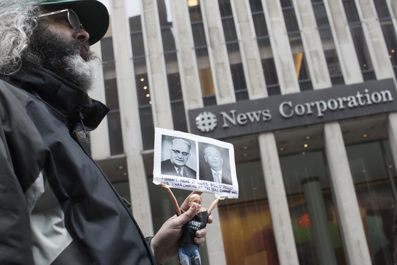 "Activist Judah Friedlander holds his ""Activist Barbie"" with a photo of Bill O'Reilly, right, next to politician Bull Connor, who strongly opposed activities of the American Civil Rights Movement in the 1960s, in front of the News Corp. headquarters in Midtown Manhattan, Wednesday, April 19, 2017. O'Reilly has lost his job at Fox News Channel after allegations that he sexually harassed women. (AP Photo/Mary Altaffer)"