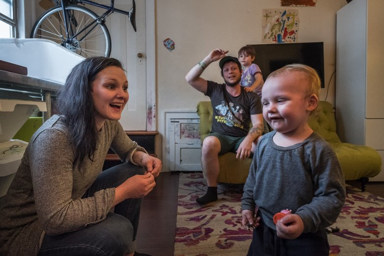 Merlée Sherman and her partner, Brandan Roe, are raising Riot, 2, and Pierce, 5, in a 250-square foot apartment in Belltown. They are worried that a Seattle City Council vote on upzoning Monday could squeeze working families out of the neighborhood. The upzone includes lower affordable-housing requirements than in other neighborhoods. (Dean Rutz/The Seattle Times)