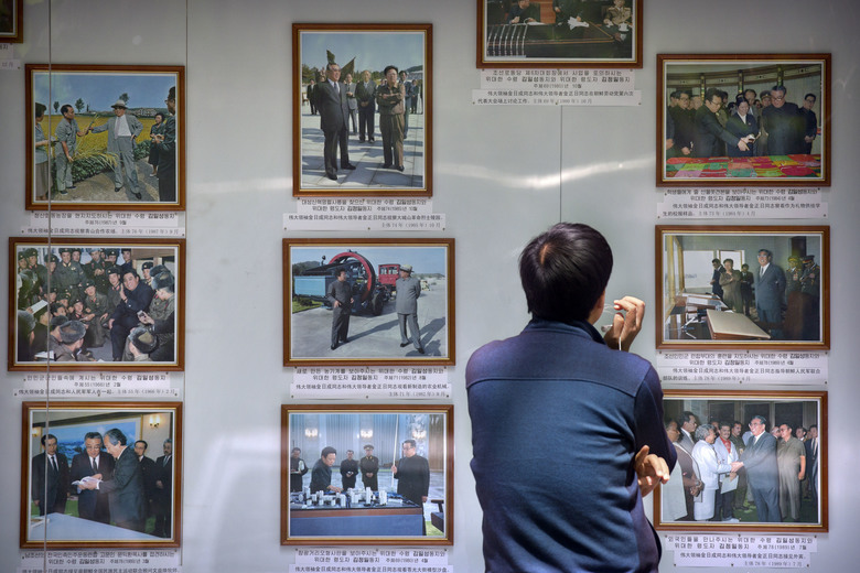 A man looks at a display board featuring photos of late North Korean leaders Kim Il Sung and Kim Jong Il outside of the North Korean Embassy in Beijing, Thursday, April 20, 2017. The U.S. is piling the pressure on Beijing to use its clout with North Korea to rein in its nuclear and missile programs. China is the North's most important trading partner and ally, but Pyongyang has ignored Beijing's calls for a suspension of those programs and its requests for high-level bilateral talks. (AP Photo/Mark Schiefelbein)