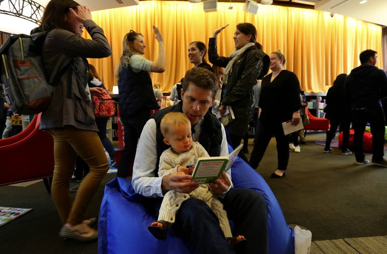 Amazon employee Pete Longhurst reads to his 9-month-old son Cal at the company's celebration of World Book Day. Amazon employees donated books for a free library at the event, which was open to employees and the community. (Alan Berner/The Seattle Times)