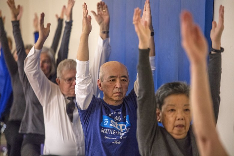 Martin Oiye, in blue, and Susan Nakagawa, front, raise their arms during a Gentle Yoga class at the Montlake Community Center. (Steve Ringman/The Seattle Times)