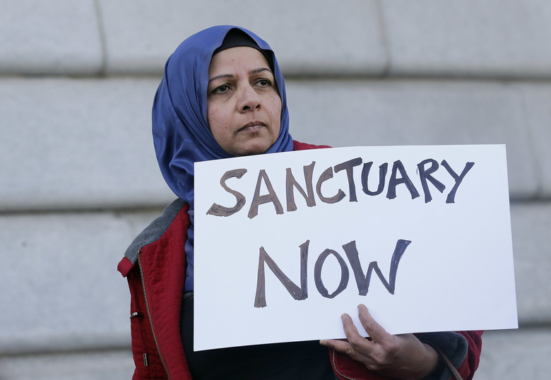FILE – In this Jan. 25, 2017 file photo, Moina Shaiq holds a sign at a rally outside of City Hall in San Francisco. On Tuesday, April 25, 2017, a federal judge blocked a Trump administration order to withhold funding from communities that limit cooperation with U.S. immigration authorities, saying the president has no authority to attach new conditions to federal spending. (AP Photo/Jeff Chiu, File)