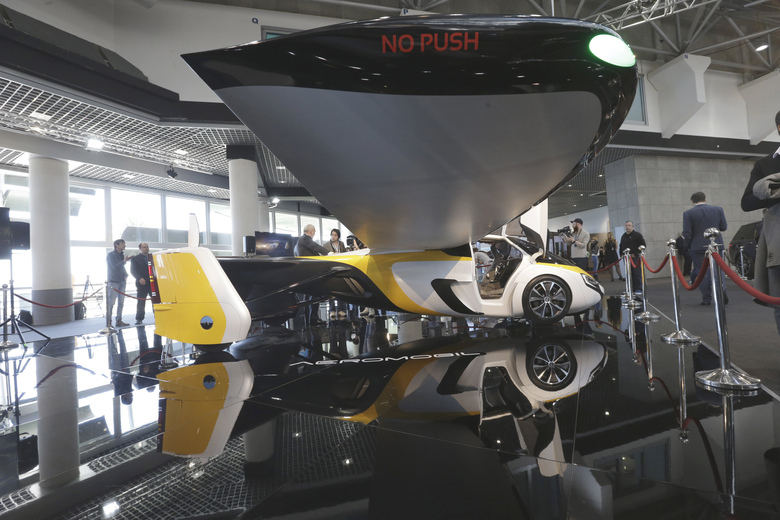 AeroMobil display their latest prototype of a flying car, in Monaco, Thursday, April 20, 2017. The light frame plane whose wings can fold back, like an insect is boosted by a rear propeller. The company says it is planning to accept first preorders for the vehicle as soon as later this year. (AP Photo/Claude Paris)