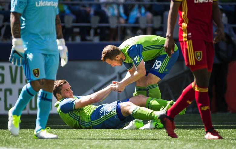 Harry Shipp helps up teammate Jordan Morris after Morris was fouled in the box in the second half, leading to a penalty kick for Seattle.  (Dean Rutz / The Seattle Times)