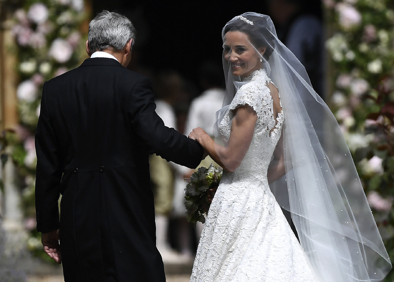 Pippa Middleton, right, is escorted by her father Michael Middleton, as she arrives for her wedding to James Matthews, at St Mark's Church in Englefield, England, Saturday, May 20, 2017. Middleton, the younger sister of Kate, Duchess of Cambridge is to marry hedge fund manager James Matthews in a ceremony Saturday where her niece and nephew Prince George and Princess Charlotte are in the wedding party, along with sister Kate and princes Harry and William. (Justin Tallis/Pool Photo via AP)