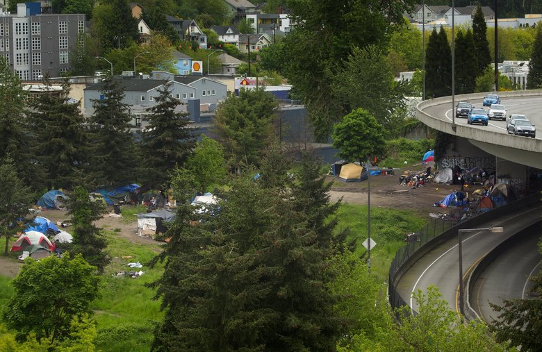 The city of Seattle will be clearing out the large homeless encampment in the greenbelt near South Dearborn Street and Rainier Avenue South on Tuesday. Tents and debris can be seen in this view south of Dearborn on Monday. Interstate 90 is on the right.  (Ellen M. Banner/The Seattle Times)
