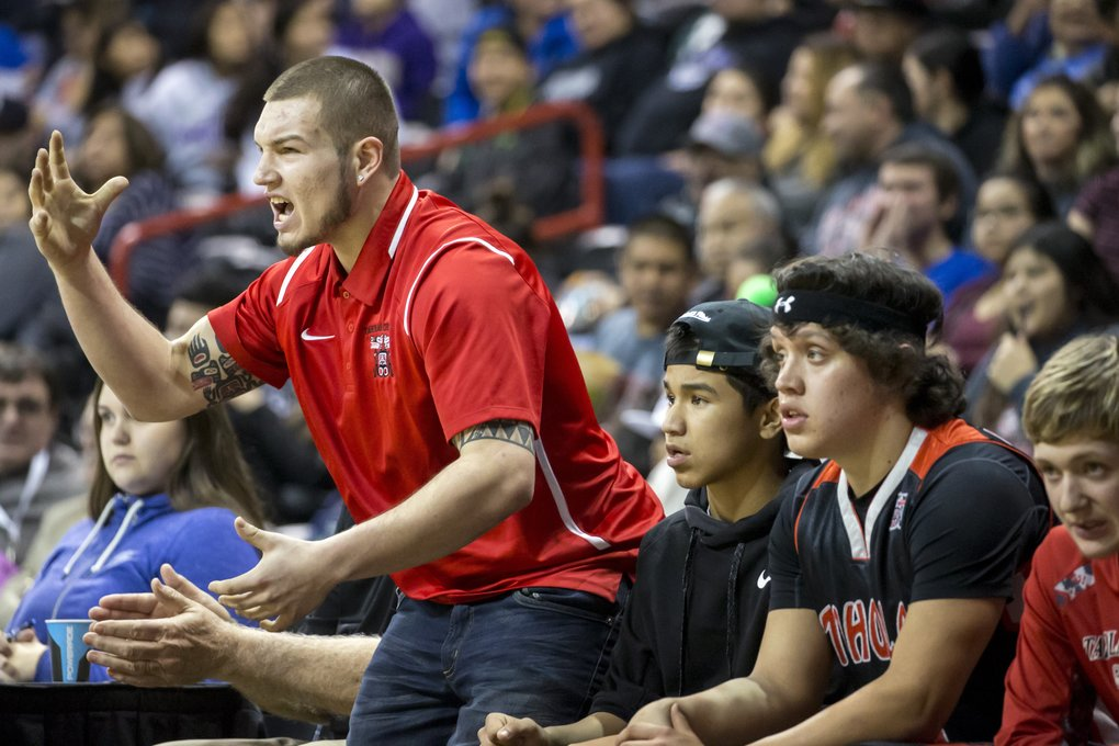 Taholah assistant coach and former player Keanu Curleybear yells from the bench during the state tournament. (Bettina Hansen/The Seattle Times)