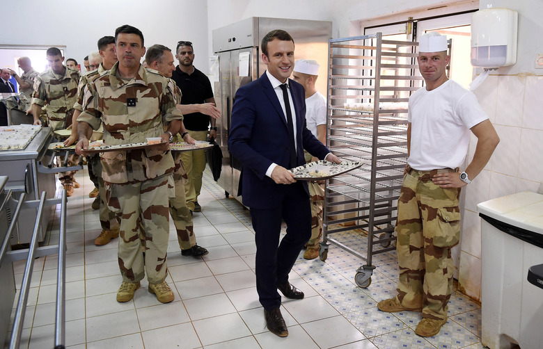 French President Emmanuel Macron lines up for food as he shares a lunch break with soldiers of Operation Barkhane, France's largest overseas military operation, in Gao, northern Mali, Friday, May 19, 2017. On his first official trip outside Europe, new French President Emmanuel Macron is highlighting his determination to crush extremism with a visit to French-led military forces combating jihadist groups in West Africa. (Christophe Petit Tesson, Pool via AP)