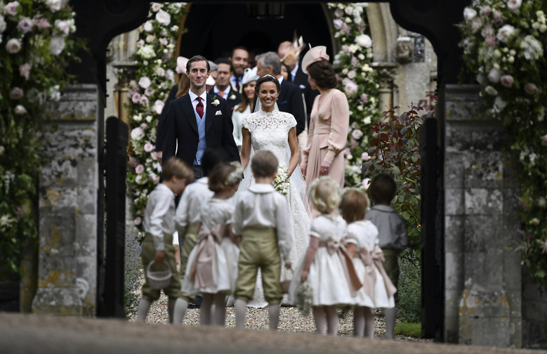 Pippa Middleton, centre, and James Matthews smile, after their wedding at St Mark's Church in Englefield, England Saturday, May 20, 2017. Middleton, the sister of Kate, Duchess of Cambridge married hedge fund manager James Matthews in a ceremony Saturday where her niece and nephew Prince George and Princess Charlotte was in the wedding party, along with sister Kate and princes Harry and William. (Justin Tallis/Pool Photo via AP)